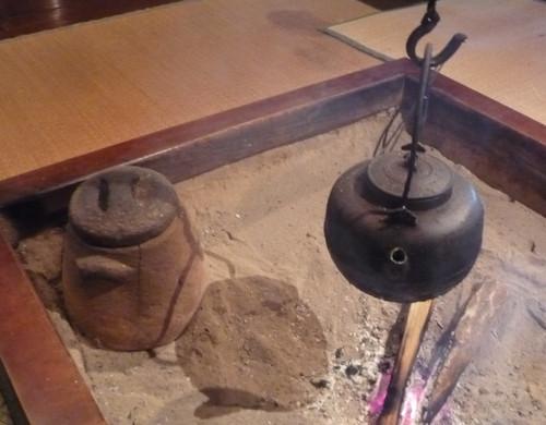資料館のいろり 左は素焼きの炭壺